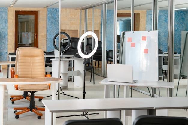 Pusta sala lekcyjna bez uczniów ze sprzętem do strumieniowego przesyłania lekcji online laptop biała lampa pierścieniowa i smartfon do spotkań online i edukacji puste biurka edukacja online