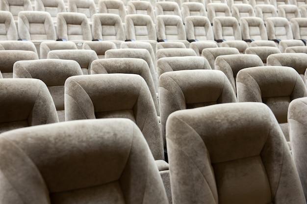 Pusta sala z beżowymi krzesłami, teatrem lub salą konferencyjną