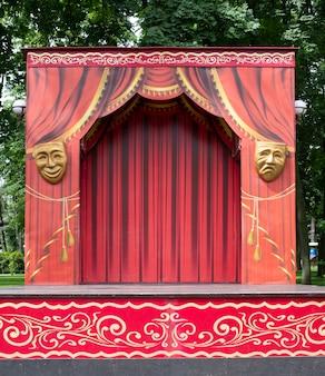 Pusta scena teatralna w parku. czerwona scena na występy. tło.
