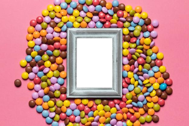 Pusta srebrna ramka nad kolorowymi cukierkami na różowym tle