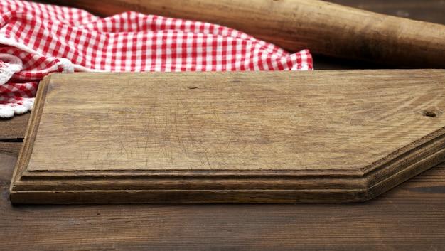 Pusta stara drewniana deska do krojenia i złożona czerwono-biała bawełniana serwetka kuchenna na drewnianym brązowym tle, widok z góry