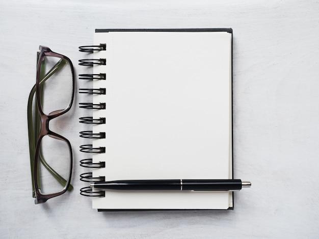 Pusta strona notatnika, długopis i okulary. kartka z życzeniami. zbliżenie, widok z góry, powierzchnia drewniana.