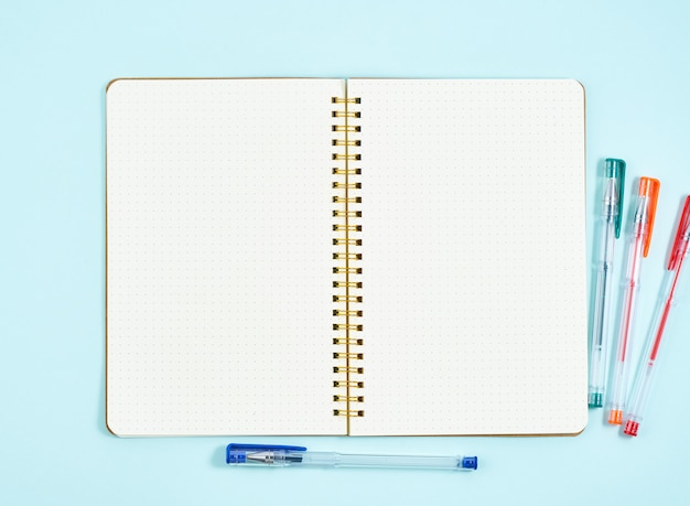 Pusta strona notatnika w dzienniku pocisku na niebieskim biurku biurowym. odgórny widok nowożytny jaskrawy stół