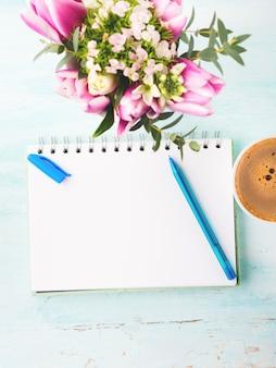 Pusta strona notebooka z niebieskim pióro i filiżanka kawy kwiaty