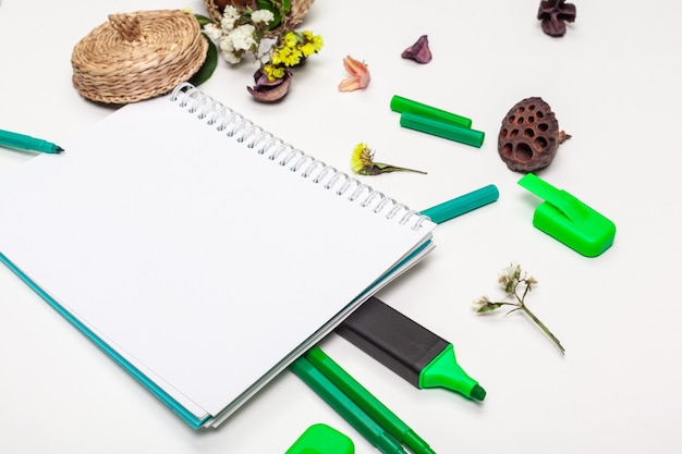 Pusta strona ślimakowaty notepad na bielu stole. kredkowy ołówek i długopis leżały płasko. pusta strona szkicownika w widoku blatu.