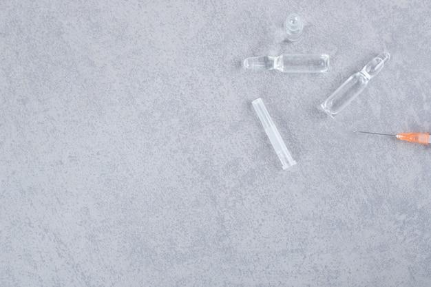Pusta strzykawka z medycznymi płynnymi pigułkami na szarej powierzchni