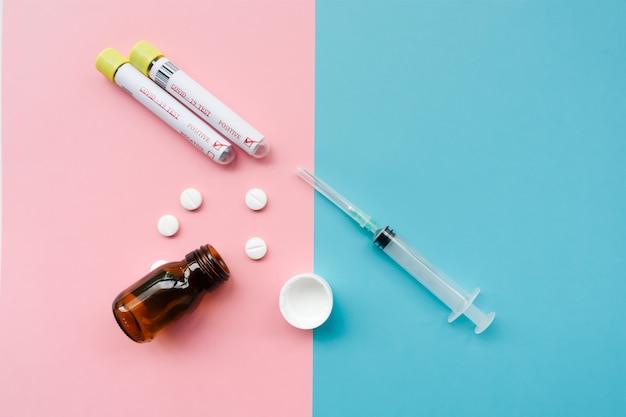 Pusta szklana butelka z tabletkami, dwoma dodatnimi testami na koronawirusa i strzykawkami. różowy i turkusowy minimalistyczny koncepcja tła