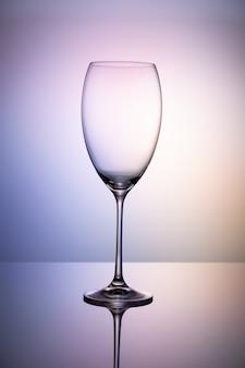 Pusta szklana czara bez wina na cienkiej nodze stoi na lustrzanej powierzchni. kolorowe fioletowe tło.