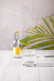 Pusta szklanka na stole i mała butelka wody tonicznej