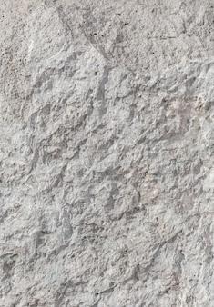 Pusta szorstka nierówna tekstura szarej betonowej ściany z bliska z miejsca na kopię