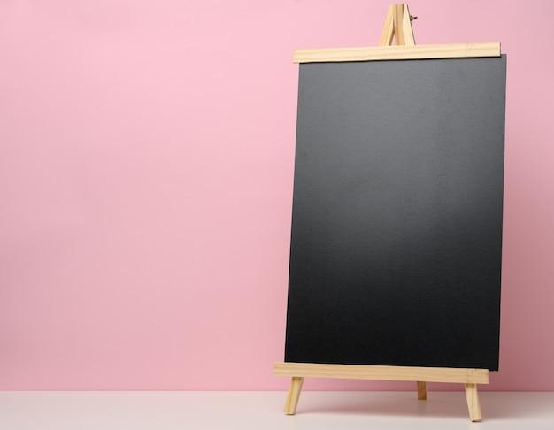 Pusta tablica łupków czarny na biały stół, różowe tło. miejsce na napis ogłoszenia
