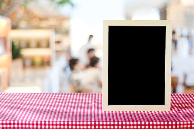 Pusta tablica stojący na czerwony i biały obrus na rozmycie restauracja