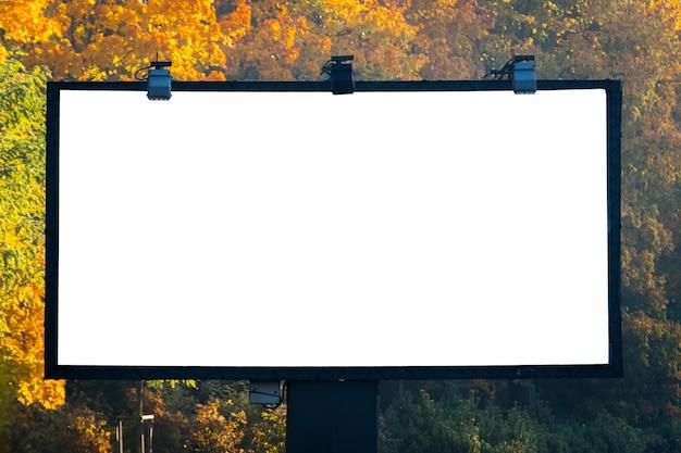 Pusta tablica z copyspace otoczona lasem na zewnątrz po stronie ulicy.
