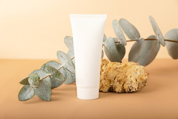 Pusta tubka kosmetyczna na pastelowym tle izometrycznymkamień naturalny i gałąź eukaliptusa w pobliżu