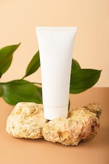 Pusta tubka kosmetyczna pozostająca na naturalnych kamieniach ozdobnych świeża zielona gałązka z tyłu