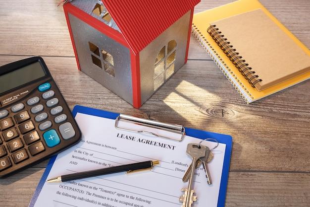 Pusta umowa najmu nieruchomości, modele domów, klucze i kalkulator na biurku