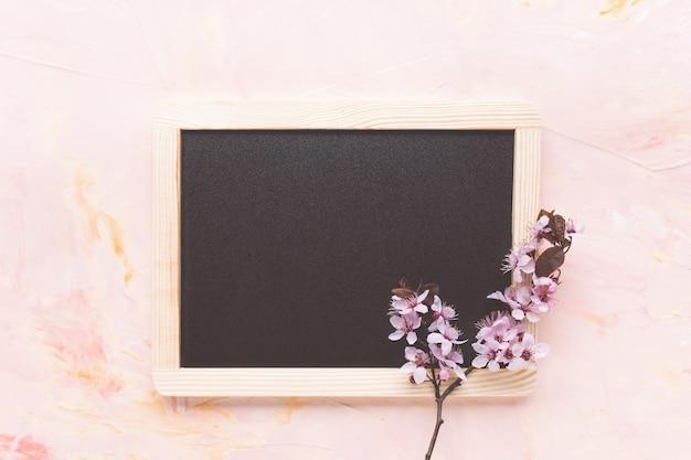 Pusta wiadomość czarna tablica i świeże wiosenne kwiaty na jasnoróżowym tle