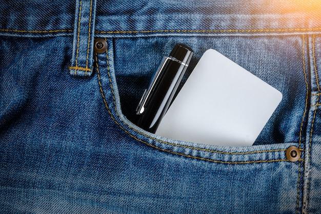 Pusta wizytówka, karta kredytowa i pióro w kieszeni jeansów