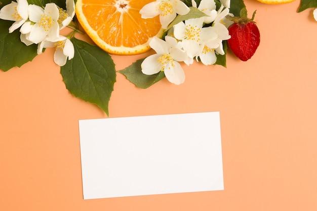Pusta wizytówka lub zaproszenie i plasterki cytrusów i truskawek z ogrodowymi kwiatami jaśminu z ...