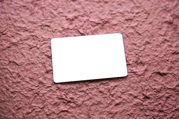 Pusta wizytówka na białym tle na teksturowanym tle magenta