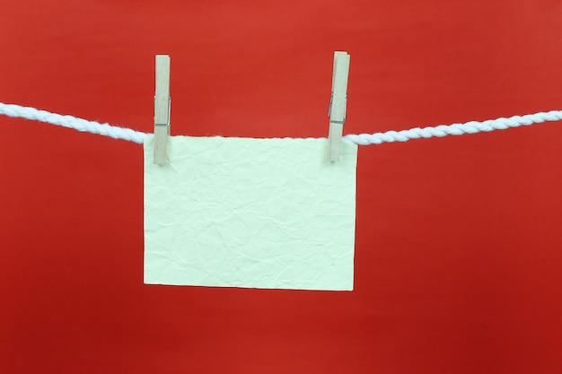Pusta zielona kartka papieru powiesiła się na sznurku.