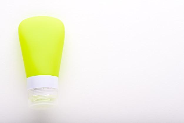 Pusta żółta kosmetyczna tubka kremu na białym tle do brandingu z miejsca na kopię