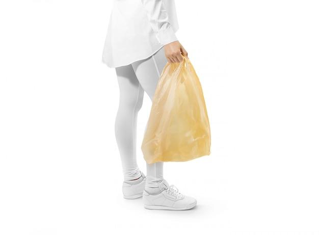 Pusta żółta plastikowa torba trzyma rękę