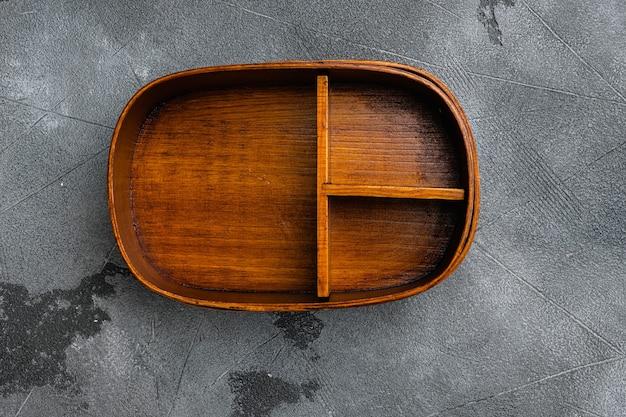Puste azjatyckie pudełko na jedzenie bento z kopią miejsca na tekst lub jedzenie z kopią miejsca na tekst lub jedzenie, widok z góry płaski, na szarym tle stołu z kamienia