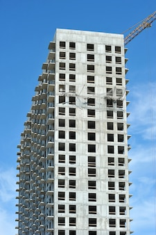 Puste betonowe pudełko wysokiego budynku i dźwig budowlany