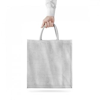 Puste białe bawełniane torby projekt eco na białym tle, trzymając rękę