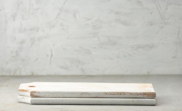 Puste białe drewniane kwadratowe deski do krojenia na szarej powierzchni, miejsce na temat