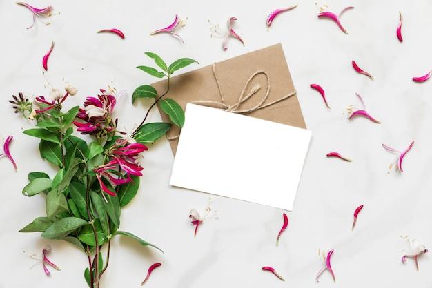 Puste białe kartkę z życzeniami w ramce z różowe kwiaty wiciokrzewu na białym marmurowym stole