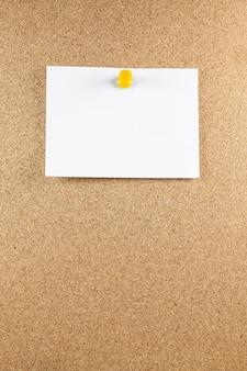 Puste białe kartki są przypięte do tablicy korkowej.