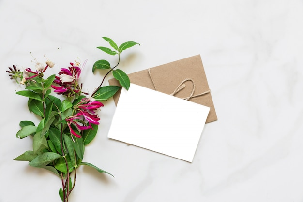 Puste białe karty z pozdrowieniami z bukietem kwiatów wiciokrzewu różowy na białym marmurowym stole z miejsca kopiowania. widok z góry