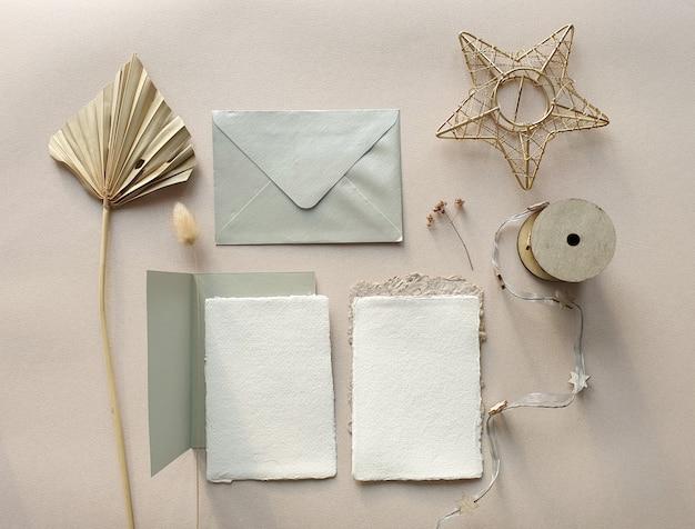 Puste białe makiety zaproszenia ślubne z suszonych liści palmowych i koperty rzemiosła na teksturowanej tabeli backgound. elegancki, nowoczesny szablon tożsamości marki. tropikalny design. leżał płasko, widok z góry