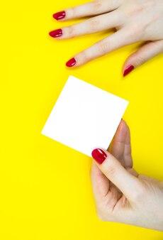 Puste białe naklejki listy rzeczy do zrobienia w ręce kobiety. zamknij się z papieru uwaga przypomnienie na żółtym tle.