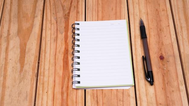 Puste białe notatki z pióra na stole z drewna