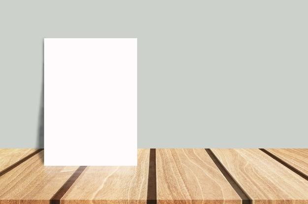 Puste białe plakat pochylony w tropikalnym drewna blat z szarej ścianie.