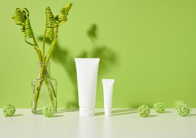 Puste białe plastikowe tuby na kosmetyki na białym stole, zielonym tle, wystrój roślin. opakowania na krem, żel, serum, reklamę i promocję produktu
