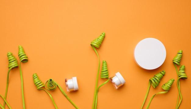 Puste białe szklane słoiki z plastikową pokrywką na pomarańczowym tle z zielonym wystrojem. opakowania na krem, żel, serum, reklamę i promocję produktu. makieta