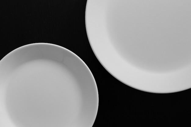 Puste białe talerze na czarnym drewnianym stole. narzędzia kuchenne z bliska