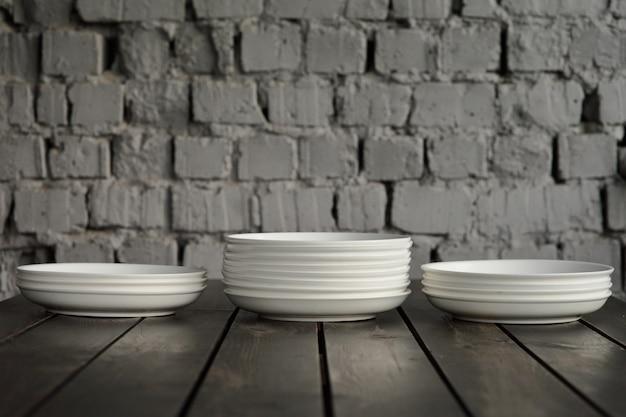 Puste białe talerze na drewnianym stole na poddaszu. wysokiej jakości zdjęcie