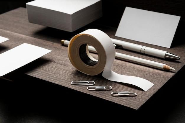 Puste białe wizytówki i taśma klejąca na drewnianym biurku