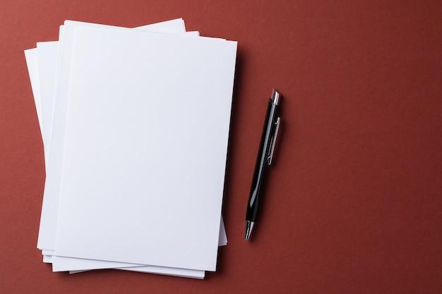Puste białe wizytówki na papierze bordowym, widok z góry