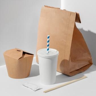 Puste chińskie opakowanie fast food pod wysokim kątem z kubkiem i pustą papierową torbą