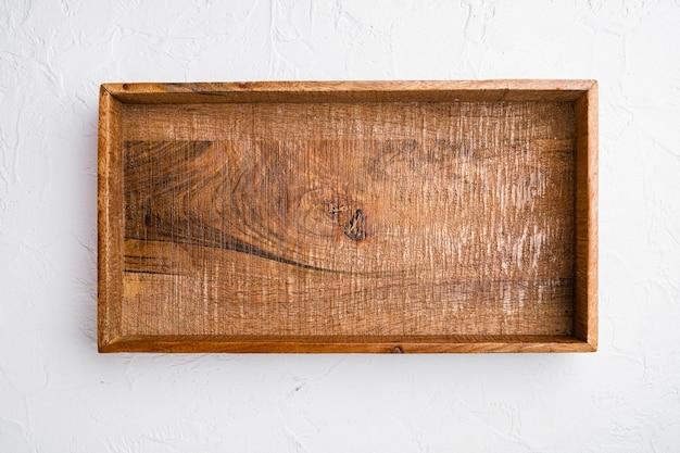 Puste ciemne drewniane pudełko z kopią miejsca na tekst lub jedzenie, widok z góry płasko leżał, na białym tle kamiennego stołu