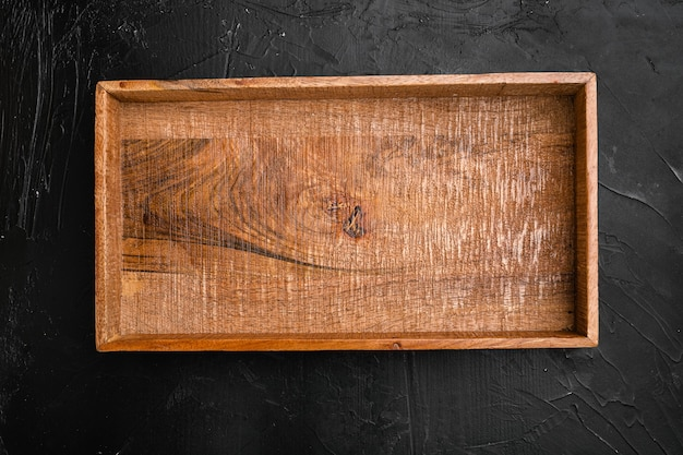 Puste ciemne drewniane pudełko z kopią miejsca na tekst lub jedzenie, widok z góry płasko leżał, na czarnym ciemnym tle kamiennego stołu