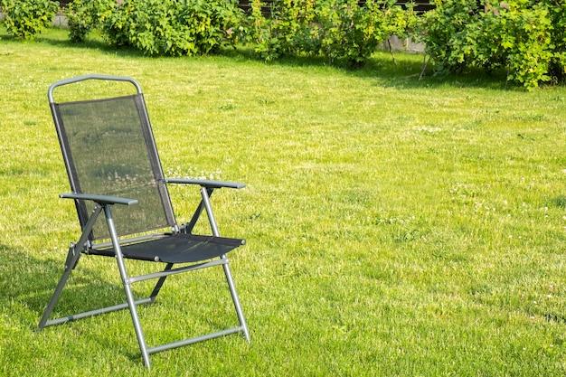 Puste czarne krzesło w ogrodzie. miejsce na tekst