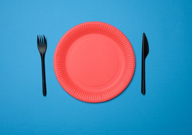Puste czerwone papierowe jednorazowe talerze na niebieskim tle, widok z góry