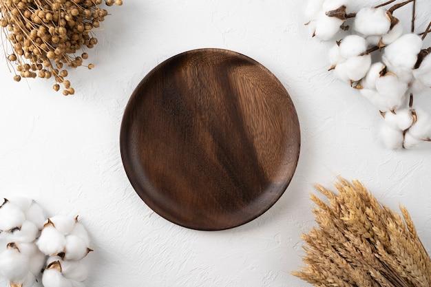 Puste danie drewniane na tle stołu z gałązką bawełny i pszenicy karta menu dla restauracji